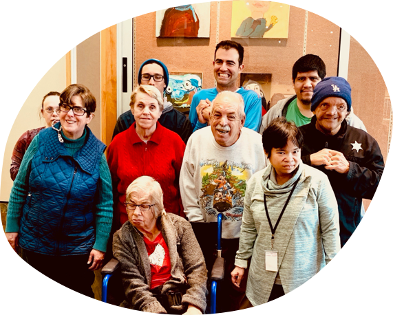Group of ten HOPE center artists in three rows smiling for photo in front of gallery of paintings.