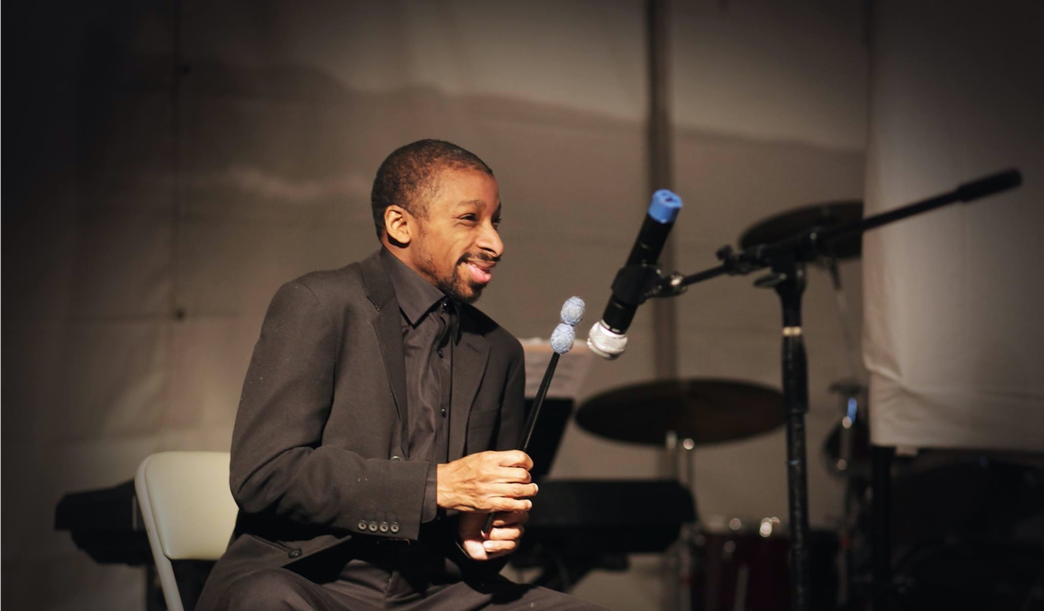 Smiling man in black suit sitting in front of microphone holding a drumstick playing music.