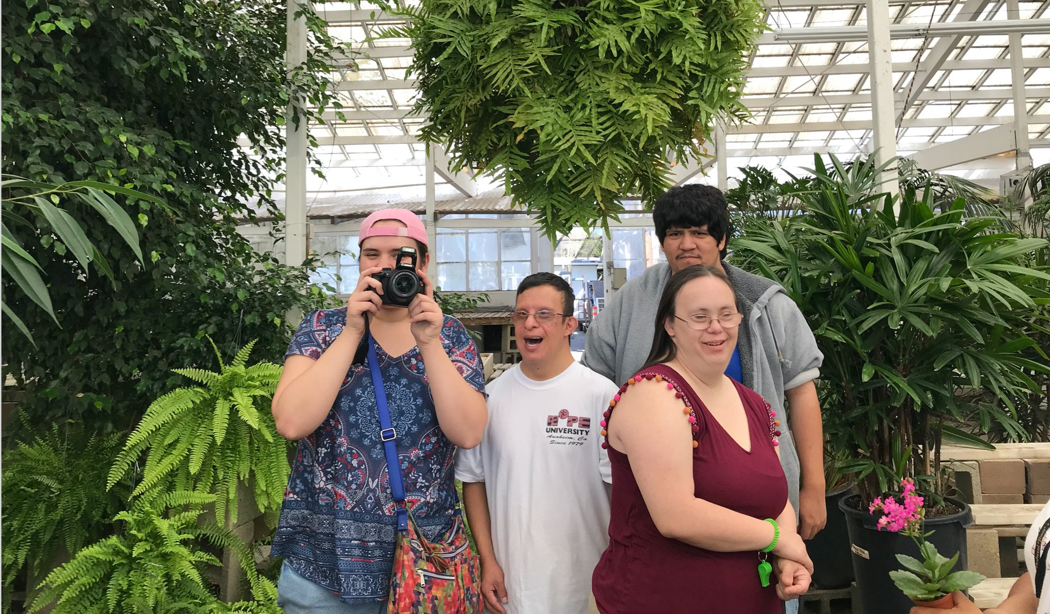 Four HOPE Center artists, one on the left holding a camera, smiling in a green plant nursery.