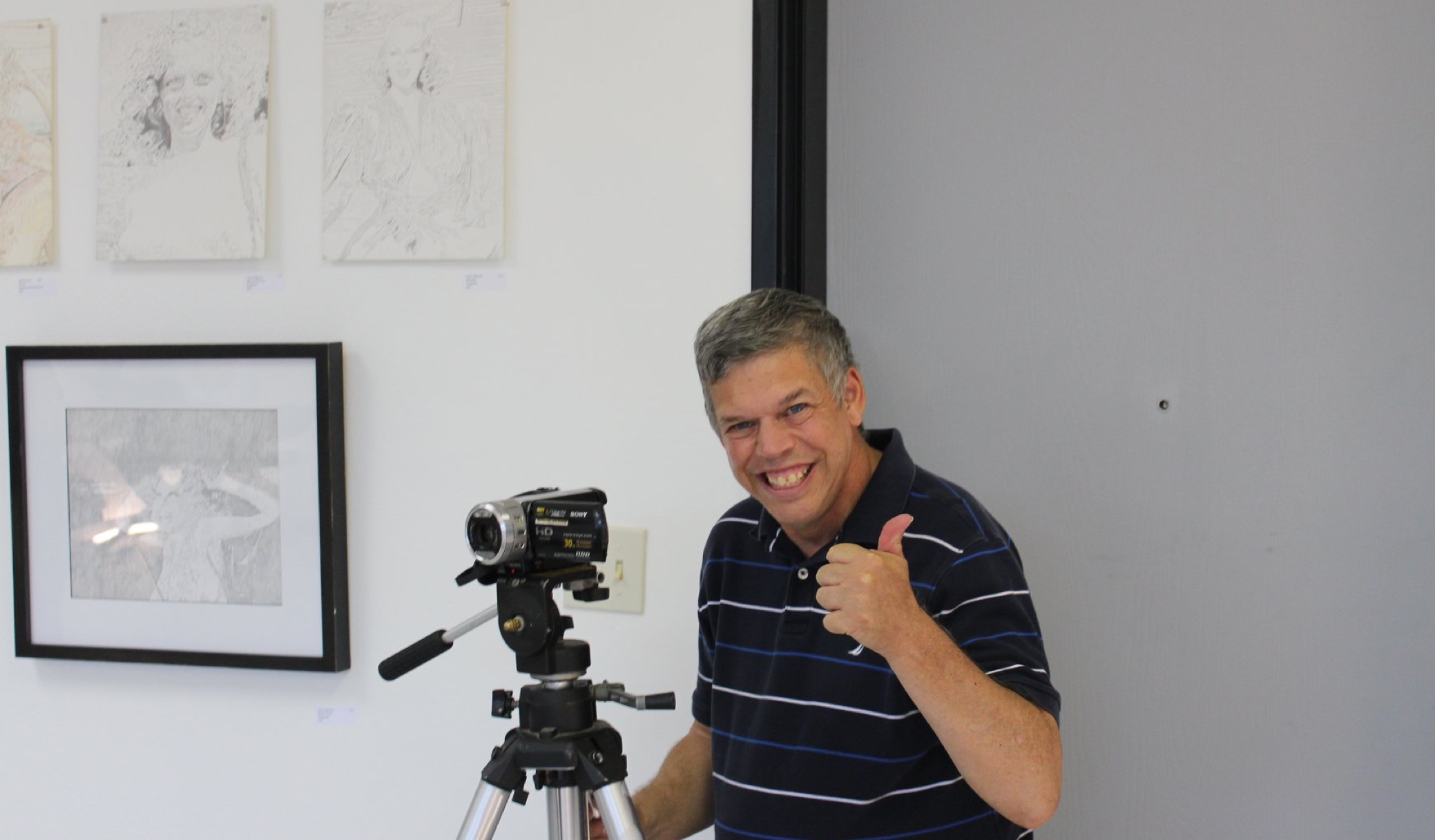 Man standing behind a video camera on tripod giving thumbs up in an art gallery.