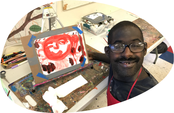Man in a red apron wearing glasses smiles in front of his painting on easel in art studio.