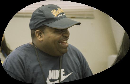 Man wearing navy baseball cap and navy Nike t-shirt and black lanyard laughing.