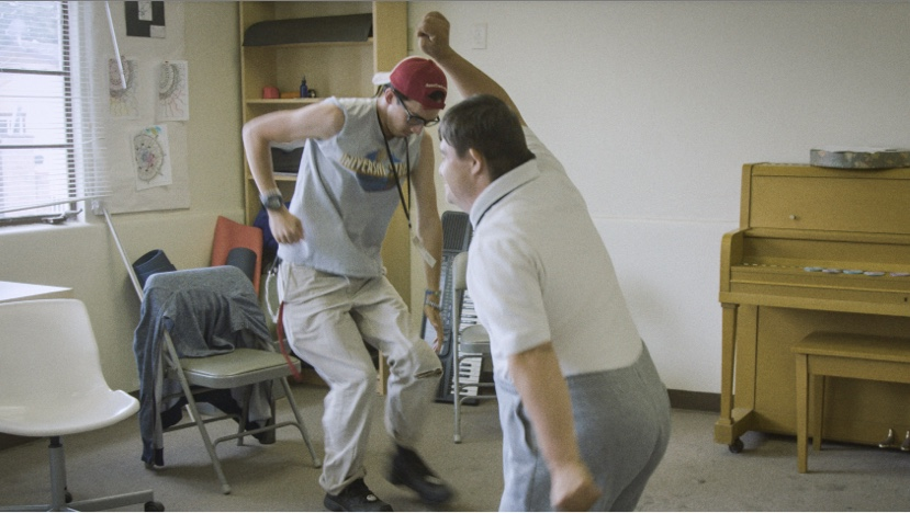Two HOPE students moving and dancing in a classroom.