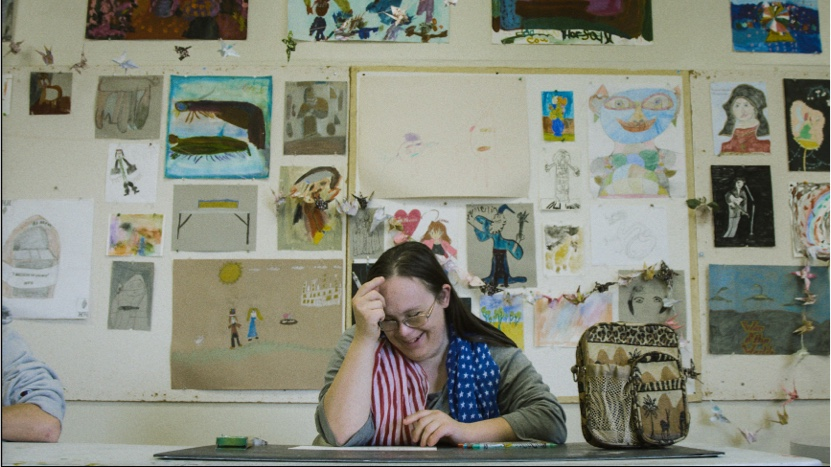 Woman sitting in art classroom wearing American flag scarf with art hung on wall in background.