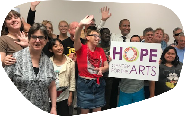 Group of HOPE students smiling and waving for photo holding up a HOPE Center for the Arts sign.